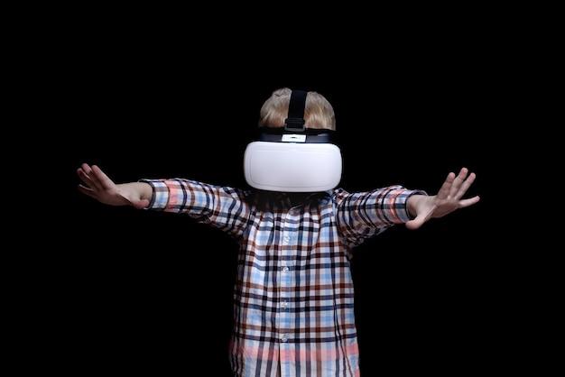 Petit garçon blond avec des lunettes de réalité virtuelle. chemise à carreaux.