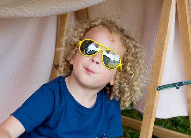 Petit garçon blond et lunettes de soleil jaunes