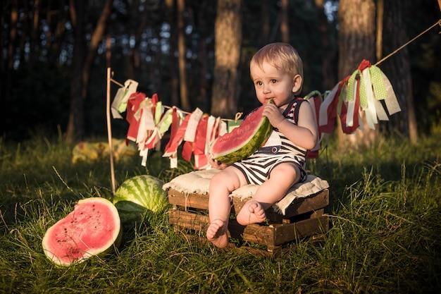 Un petit garçon blond mange une pastèque et sourit.