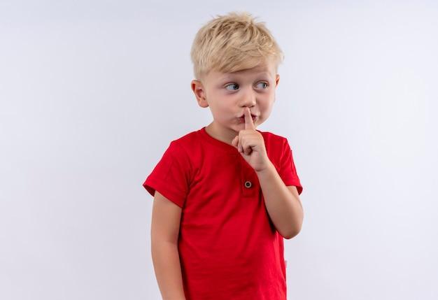 Un petit garçon blond mignon en t-shirt rouge montrant le geste chut avec l'index sur sa bouche tout en regardant côté sur un mur blanc