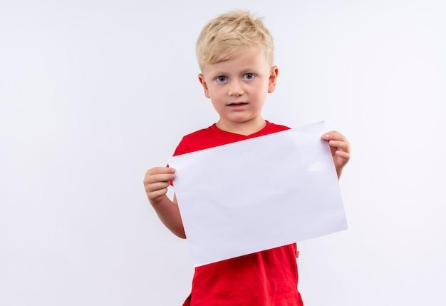 Un petit garçon blond mignon en t-shirt rouge tenant une feuille de papier vierge tout en regardant sur un mur blanc