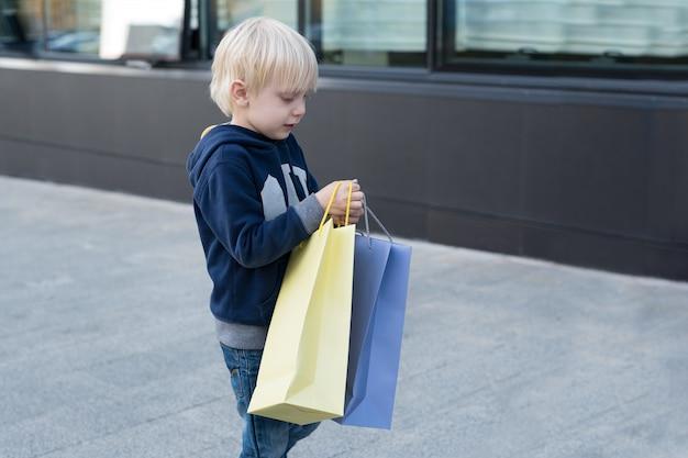 Petit garçon blond avec des sacs à provisions, shopping en famille