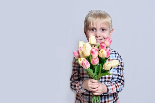 Petit garçon blond souriant tenant un bouquet de tulipes.