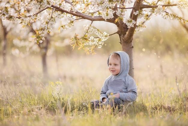 Petit garçon blond en sweat-shirt gris avec une capuche sur la tête se trouve dans l'herbe verte sous l'arbre en fleurs