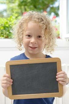 Petit garçon blond tenant un tableau