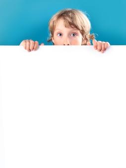Petit garçon blond avec visage surpris maintenant, à la recherche d'une pancarte blanche sur fond bleu