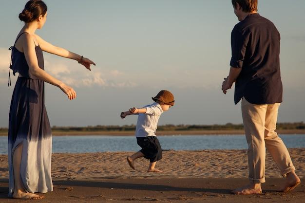 Un petit garçon en bob marron longe la plage non loin de ses parents.