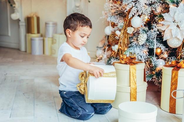 Petit garçon avec boîte-cadeau près de l'arbre de noël