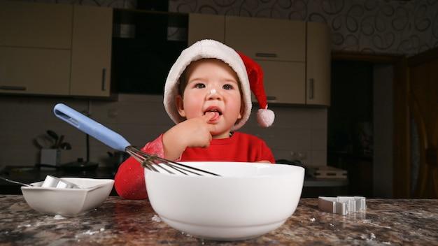 Petit garçon en bonnet de noel cuisine dans la cuisine