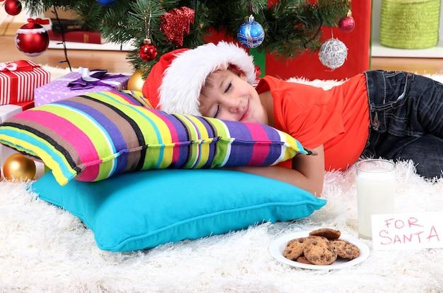 Petit garçon en bonnet de noel avec du lait et des biscuits pour le père noël