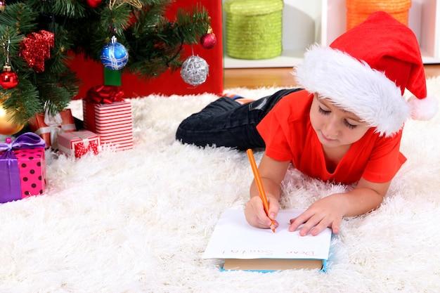 Petit garçon en bonnet de noel écrit une lettre au père noël