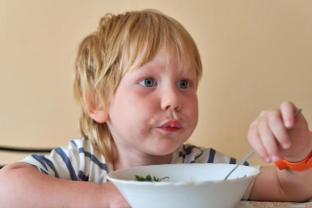 Un petit garçon avec une bouche sale mange avec une cuillère d'un plat