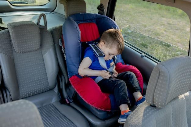 Petit garçon bouclé avec ceinture de sécurité à l'intérieur de la voiture