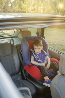 Le petit garçon a bouclé sa ceinture de sécurité à l'intérieur de la voiture. concept de véhicule et de transport