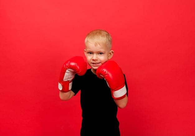 Un petit garçon boxeur en gants de boxe rouges se dresse dans un stand sur le rouge