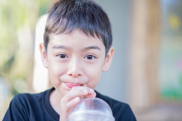 Petit garçon buvant une boisson gazeuse au lait mélangé à froid en utilisant de la paille