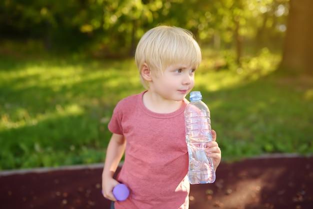 Petit garçon buvant de l'eau pendant l'entraînement avec des haltères