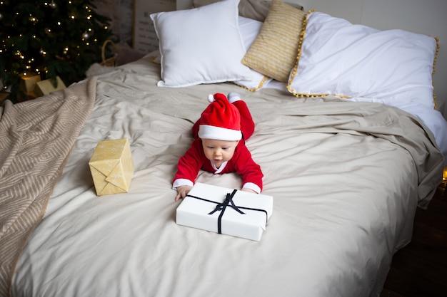 Petit garçon avec cadeau de noël sur le lit à la maison