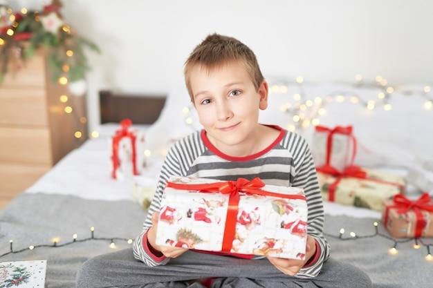 Petit garçon avec des cadeaux de noël à la maison sur un lit avec un décor de noël