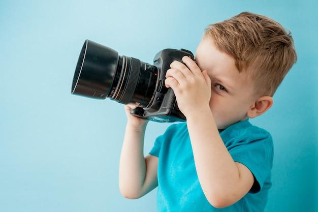 Petit garçon avec caméra sur fond bleu