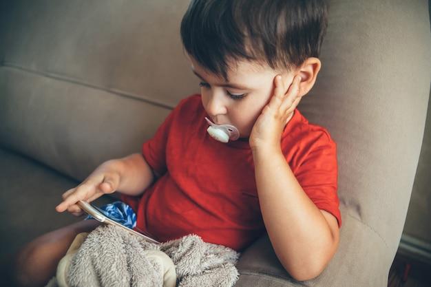 Petit garçon caucasien assis sur le lit et regardant l'écran du téléphone tout en tenant une mangeoire dans la bouche