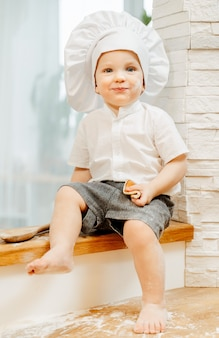 Petit garçon caucasien charmant positif dans un costume de cuisinier assis sur la table de cuisine