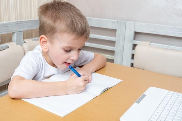 Un petit garçon caucasien concentré écrit dans un cahier faisant une leçon d'enseignant à la maison. un enfant tenant un stylo et dessinant dans un cahier à la table. retour au concept de l'école.