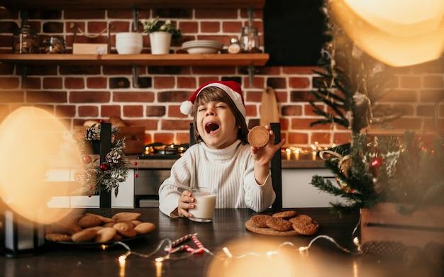 Un petit garçon caucasien dans un pull en tricot blanc et un chapeau de noël rouge est assis à la table de la cuisine avec des biscuits à l'avoine et du lait