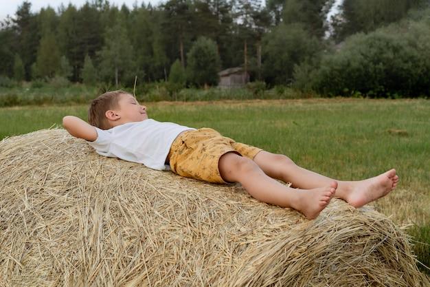 Petit garçon caucasien mignon s'étendant sur le sac de foin avec une paille dans sa bouche