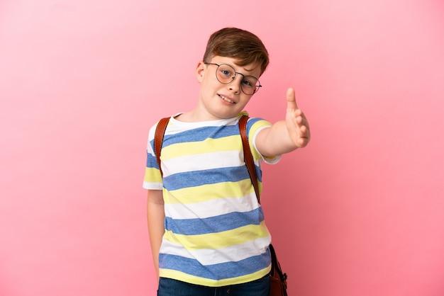 Petit garçon caucasien roux isolé sur fond rose se serrant la main pour conclure une bonne affaire