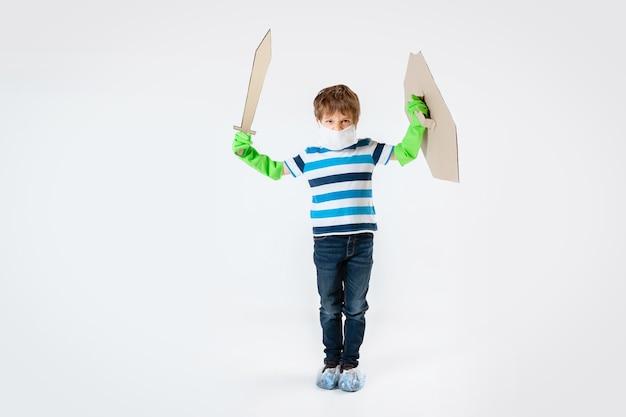 Petit garçon caucasien en tant que guerrier au combat contre la pandémie de coronavirus, avec un bouclier, une épée et une bandoulière en papier toilette. teenboy en guerre pour des vies humaines. concept d'enfance, de santé, de victoire.