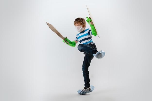 Petit garçon caucasien en tant que guerrier dans la lutte contre la pandémie de coronavirus, avec un bouclier et une épée attaquant. teenboy en masque facial en guerre pour des vies humaines. concept d'enfance, de santé, de victoire.
