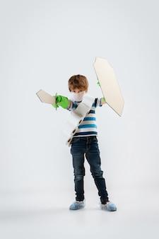 Petit garçon caucasien en tant que guerrier dans la lutte contre la pandémie de coronavirus, avec un bouclier, une lance et un bandoulière de papier toilette, attaquant