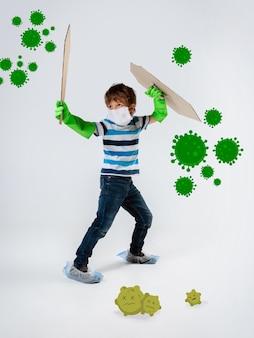 Petit garçon caucasien en tant que guerrier dans la lutte contre la pandémie de coronavirus, design lumineux avec des dessins de style dessins animés mignons et amusants. teenboy en guerre pour des vies humaines. concept d'enfance, de santé, de victoire.