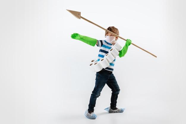 Petit garçon caucasien en tant que guerrier en lutte contre la pandémie de coronavirus, avec un masque facial, une lance et une bandoulière en papier toilette. teenboy en guerre pour des vies humaines. concept d'enfance, de santé, de victoire.