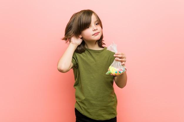 Petit garçon caucasien tenant des bonbons en essayant d'écouter un commérage
