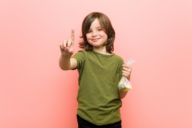 Petit garçon caucasien tenant des bonbons montrant le numéro un avec le doigt.