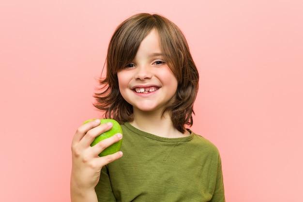 Petit garçon caucasien tenant une pomme