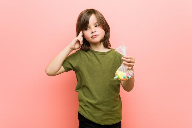Petit garçon, caucasien, tenue, bonbons, pointage, sien, temple, à, doigt