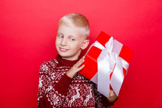 Petit garçon caucasien en vêtements tricotés traditionnels x mas, isolé sur un espace rouge, excité, regardant un cadeau, tenez-le et devinez ce qu'il y a à l'intérieur, curieux, rêveur, ne peut pas attendre pour l'ouvrir