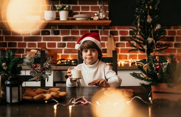 Un petit garçon caucasien vêtu d'un pull blanc et d'un chapeau du nouvel an est assis dans la cuisine avec un verre de lait et des biscuits à l'avoine