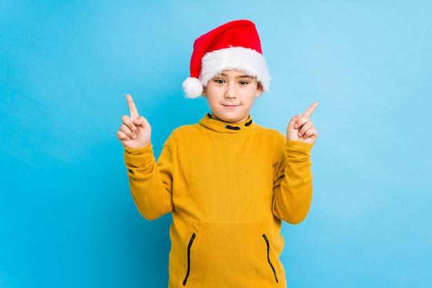 Petit garçon célébrant le jour de noël portant un bonnet de noel isolé indique avec les deux doigts devant un espace vide.
