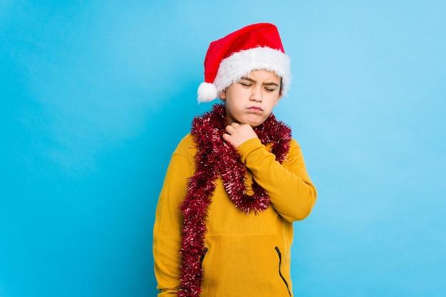 Petit garçon célébrant le jour de noël portant un bonnet de noel isolé souffre de douleurs à la gorge dues à un virus ou à une infection.