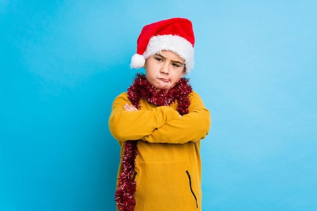 Petit garçon célébrant le jour de noël portant un bonnet de noel, visage fronçant les sourcils de déplaisir, garde les bras croisés.
