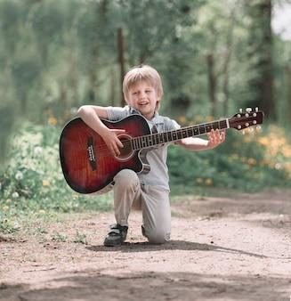 Le petit garçon chante une chanson sur le chemin du parc. le concept d'une enfance heureuse