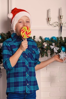 Petit garçon en chapeau de père noël tient une grosse sucette savoureuse dans sa main dans la chambre avec décoration de noël