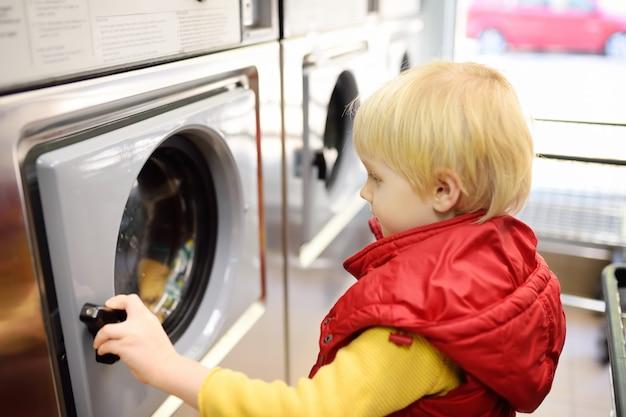 Un petit garçon charge des vêtements dans la machine à laver dans une laverie publique