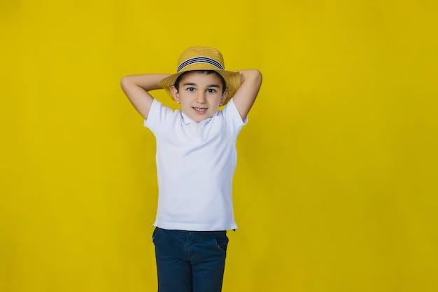 Un petit garçon en chemise blanche et chapeau de paille sur un mur jaune.
