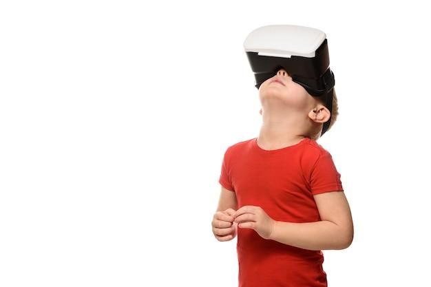 Petit garçon en chemise rouge fait l'expérience de la réalité virtuelle, levant la tête