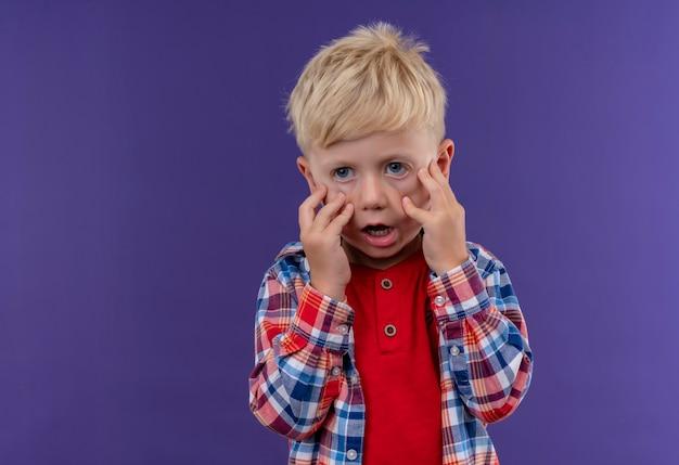 Un petit garçon choqué aux cheveux blonds portant une chemise à carreaux tenant la main sur son visage sur un mur violet